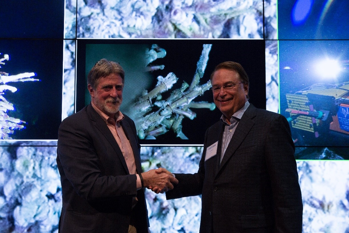 John Delaney and Larry Smarr celebrate the achievement of delivery of remote-controlled live HD video to the tiled display behind them in Clait2's Qualcomm Institute.